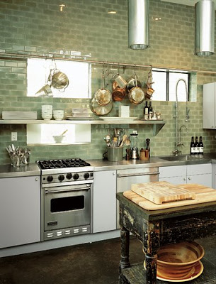 Small kitchen with open stainless steel shelf, Ann Sacks Capriccio ceramic field tiles in green backsplash, stainless counter tops and a worn looking black country table doubles as a center island