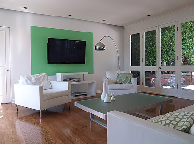 Modern dining room designed by Vanessa de Vargas with white leather armchairs and sofa, frosted glass and brushed metal coffee table, French doors with a view of a lush patio and a green color block on one wall with a flat panel TV