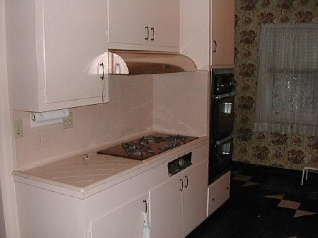 Pink kitchen with a copper stove top and hood, black ovens and floral wallpaper before remodeling by Newman & Wolen Design