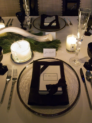 Silver rimmed glass plates frame black napkins and a Jo Malone party favor