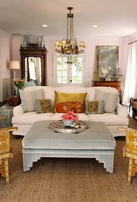 Light blue velvet ottoman in a living room with a white tight back upholstered sofa and sea grass rug by Windsor Smith
