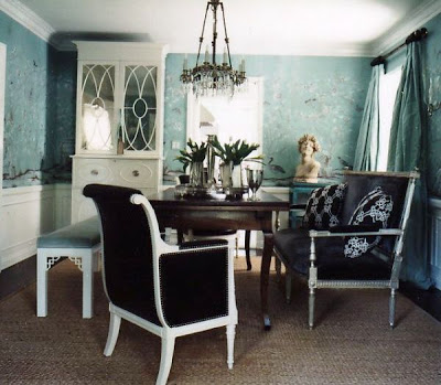 Dining room with light blue floral wallpaper, a dark brown upholstered armchair with white legs and arms and nail head trim, a white lacquer cabinet with mirrored doors, a white Chippendale bench upholstered in light blue velvet and an upholstered and wood settee by Windsor Smith