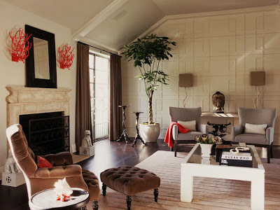 Living room with decorative molding on the main wall, marble fireplace and tufted armchair by Betsy Burnham