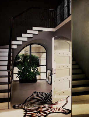 Dark brown with white trim two story entryway by Betsy Burnham with a zebra print rug