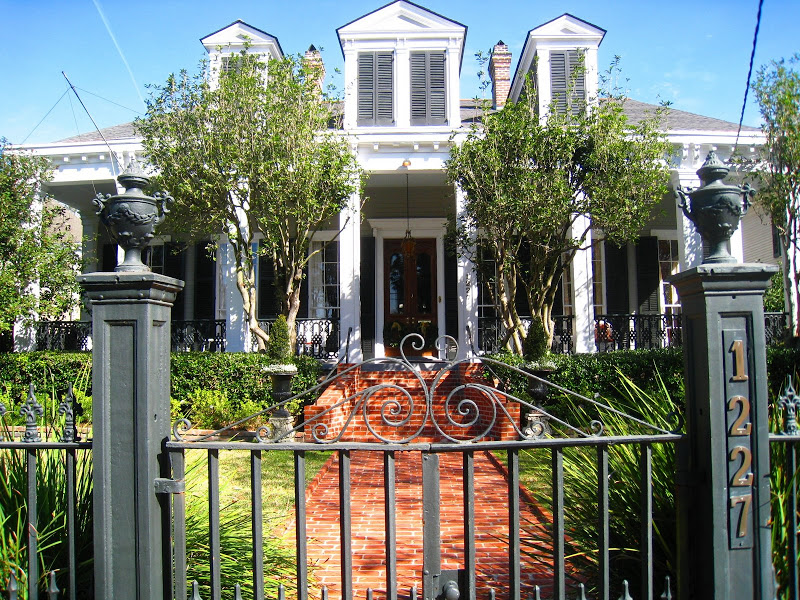 Iron gate outside a classic home with a red brick walkway and white columns