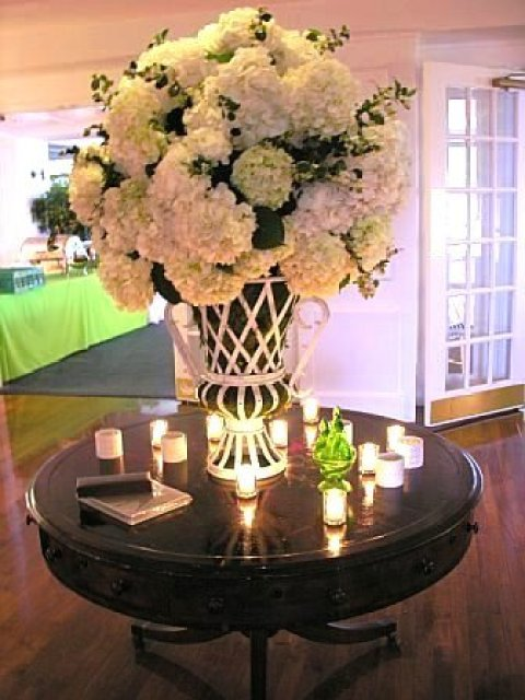 Hydrangeas for a wedding on a round dark wood table by Delaney Todd Bagwell