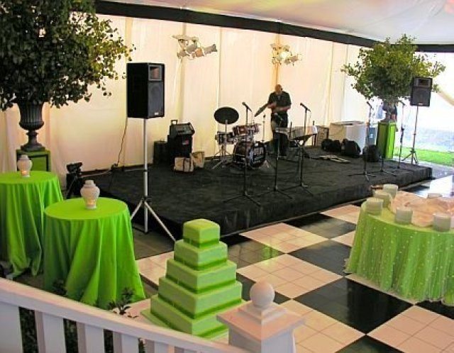 Band area at a wedding with a black and white checkered dance floor designed by Delaney Todd Bagwell
