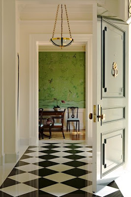 Entryway by Los Angeles interior designer Elizabeth Dinkel with black and white checkerboard floor, hunter green door with paneling, molding and a simple brass pedant