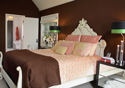 Master bedroom with white carved wood bed, pink and brown bedding and chocolate walls