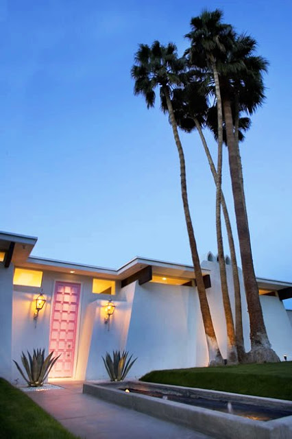 Exterior of a Palm Springs home with a pink front door at night