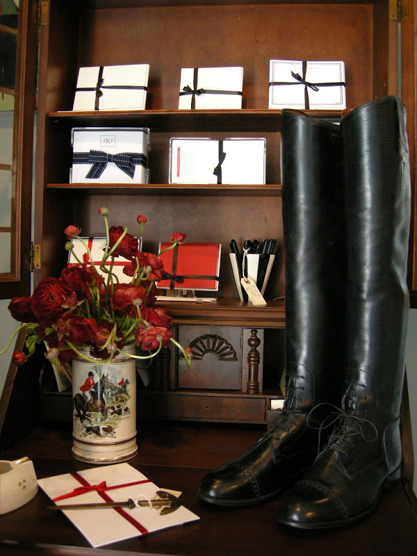Black boots in front of a shelf with neatly wrapped stationary
