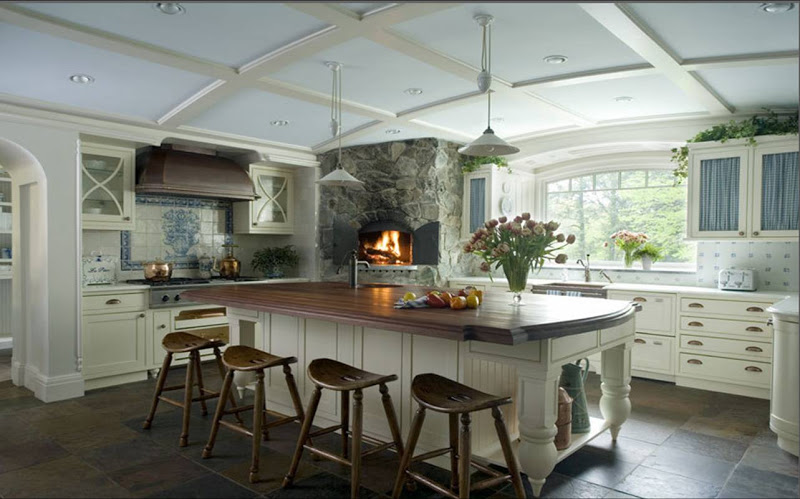 Rustic kitchen with a stone covered pizza oven, wood island counter top, bright white cabinets and drawer pulls, stone tile floor and arched coffered ceiling