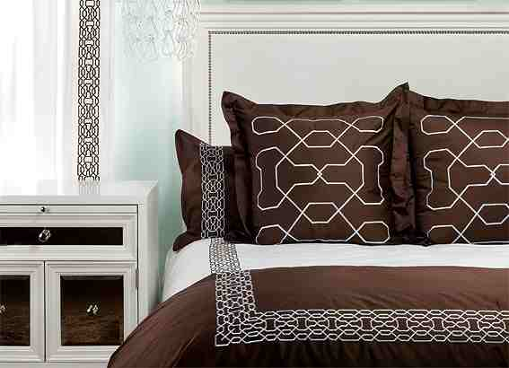 Bed with white headboard with nail head trim, brown pillows with silver embroidery and matching white and brown bedding