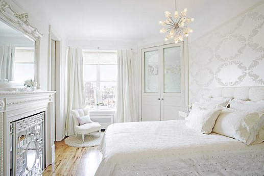 White bedroom by Kelly Giesen with a tufted headboard, patterned wallpaper, chandelier and a mirrored fireplace