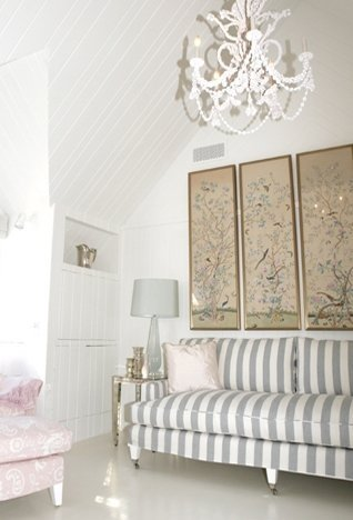 Bedroom with grey and white striped sofa, white chandelier, and framed Japanese prints