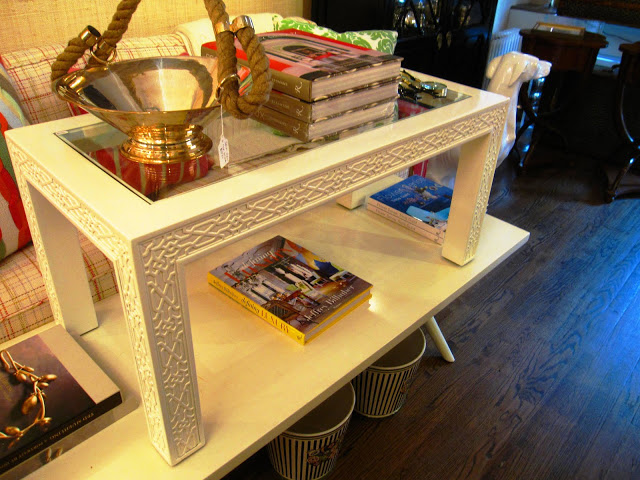 Rectangular white lacquer coffee table with glass top and carved fretwork detailing on the side and legs inside the Elizabeth Bauer store