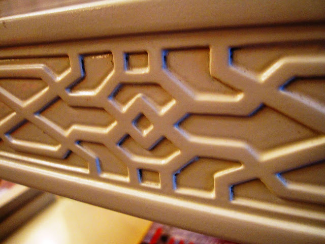 Close up of the carved geometric fretwork detailing on the side of a white lacquer coffee table inside the Elizabeth Bauer store