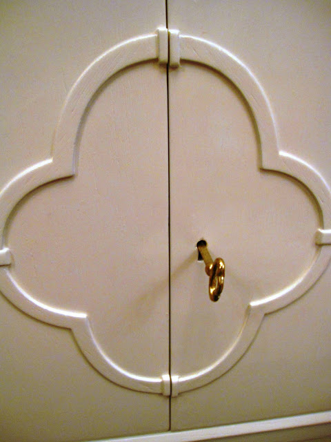 Quatrefoil design surrounding a brass key and lock on a white lacquer side table inside the Elizabeth Bauer store