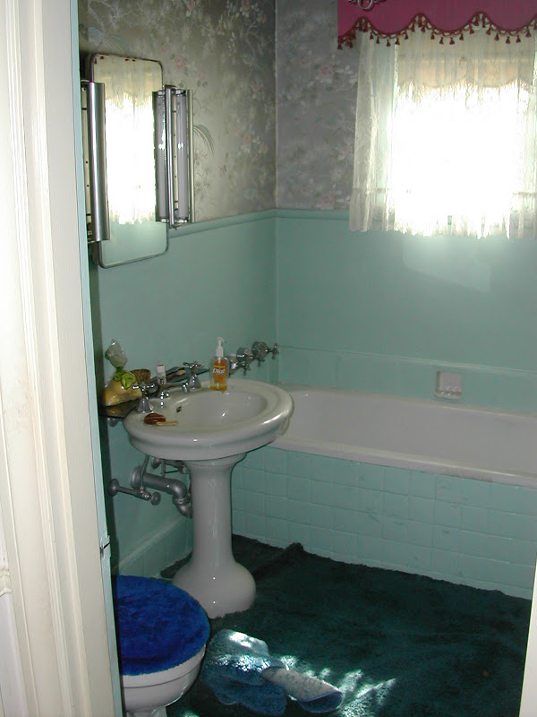 Bathroom before Newman & Wolen Design's remodeling with blue carpet, blue tiling and grey metallic wallpaper