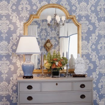 Blue bedroom with damask wallpaper, periwinkle porcelain lamp and a gold mirror above a white chest of drawers by Kelley Proxmire