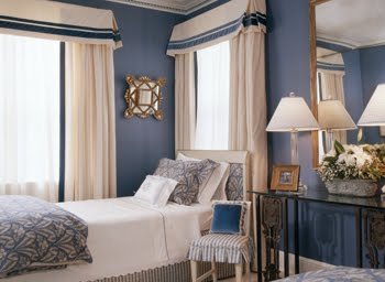 Blue bedroom by Kelley Proxmire with twin bed with a white scalloped bed cover, striped blue and white skirt and dusty blue and white blanket and pillow covers