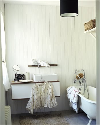 Country bathroom with white beadboard walls, floating wall mounted vanity, white claw foot tub and a black pendant light