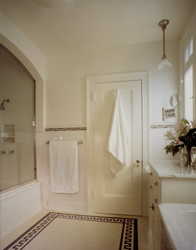Classic white bathroom by Kevin Oreck with white tile floor with a black borders and trim