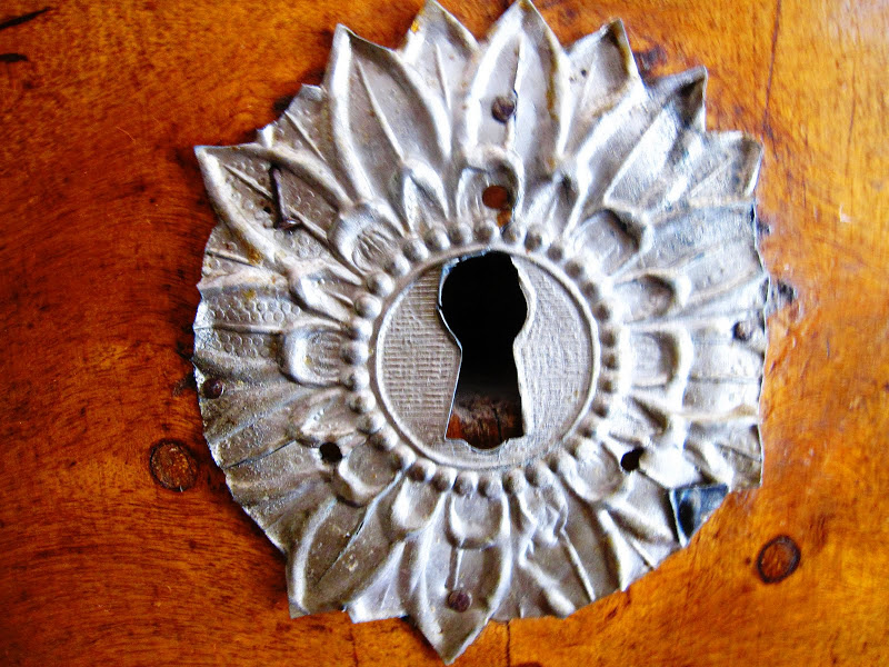 Metal key hole on a drawer on an antique dresser