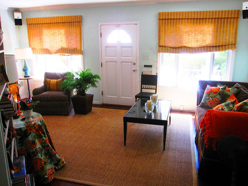 Sea foam living room with a sea grass rug, a brown sofa, patterned armchair and orange roller shades