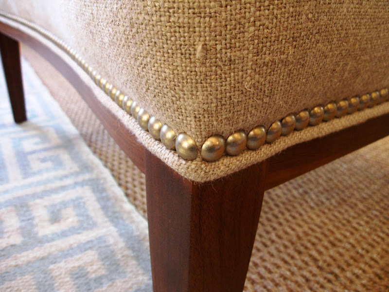 Close up of the nail head trim on a n extra wide upholstered chair in the Jonathan Adler store