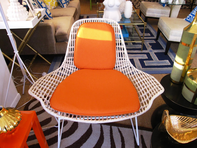 Modern woven white rattan chair on white metal frame with orange seat cushions in the Jonathan Adler store