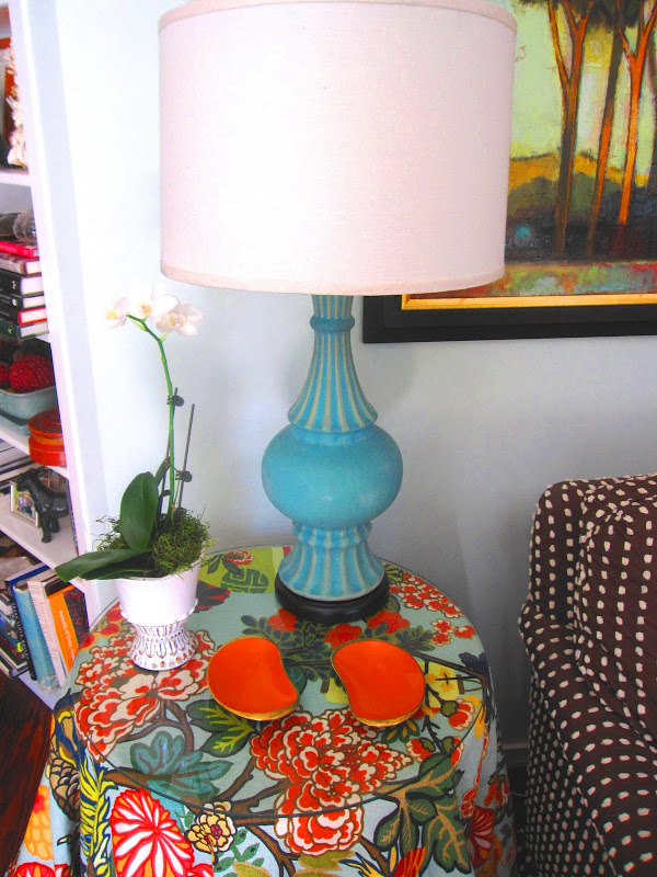 Blue vase converted into a classic table lamp on a side table with brightly colored cover