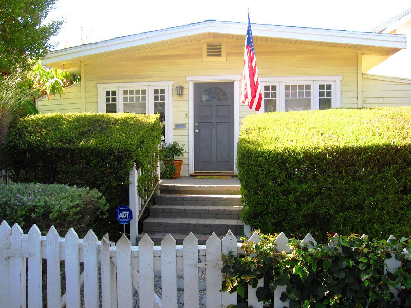 Yellow cottage with white trim and a grey door in Venice Beach, CA