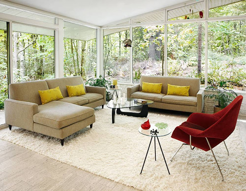 Modern living room with floor to ceiling windows, two taupe sofas with yellow accent pillows, a Noguchi glass coffee table and a red Eero Saarinen Womb Chair