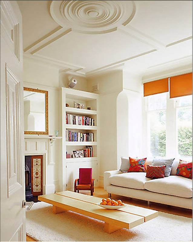 Living room with high ceilings with modern round ceiling medallion, cream walls, built in bookshelf and sofa with orange curtains