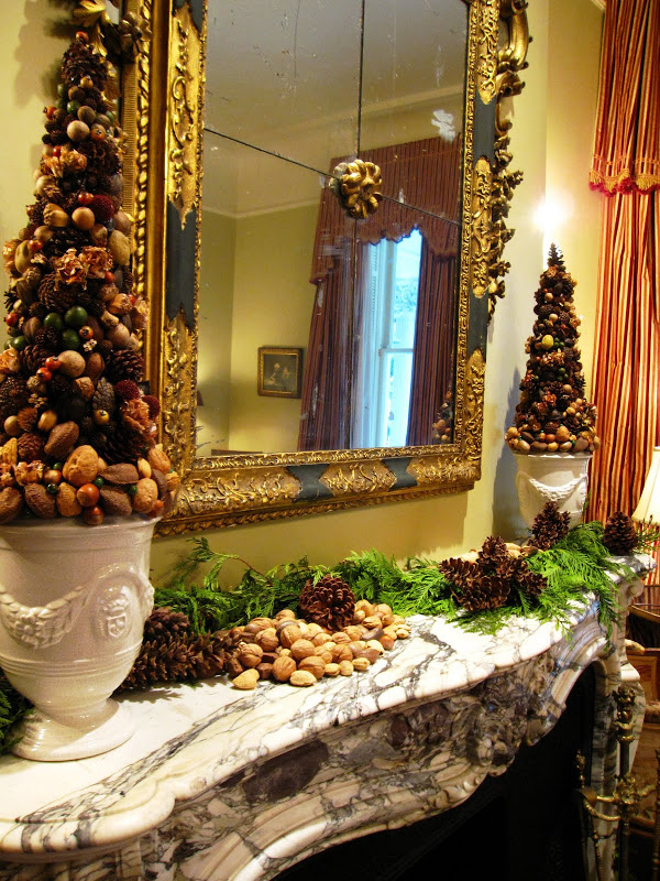 Fireplace in the men's parlor of a historic New Orleans mansion with a garland made of fresh pine, pine cones and nuts and a nut topiary