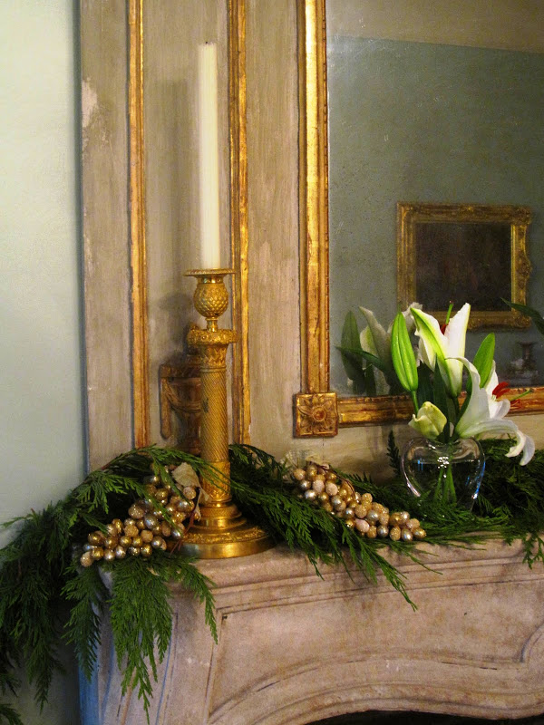 Fireplace in the ladies parlor of a historic New Orleans mansion with a garland made of a cedar/pine bows, faux frosted gold grapes, star gazer lilies in simple clear vases and gold candlesticks