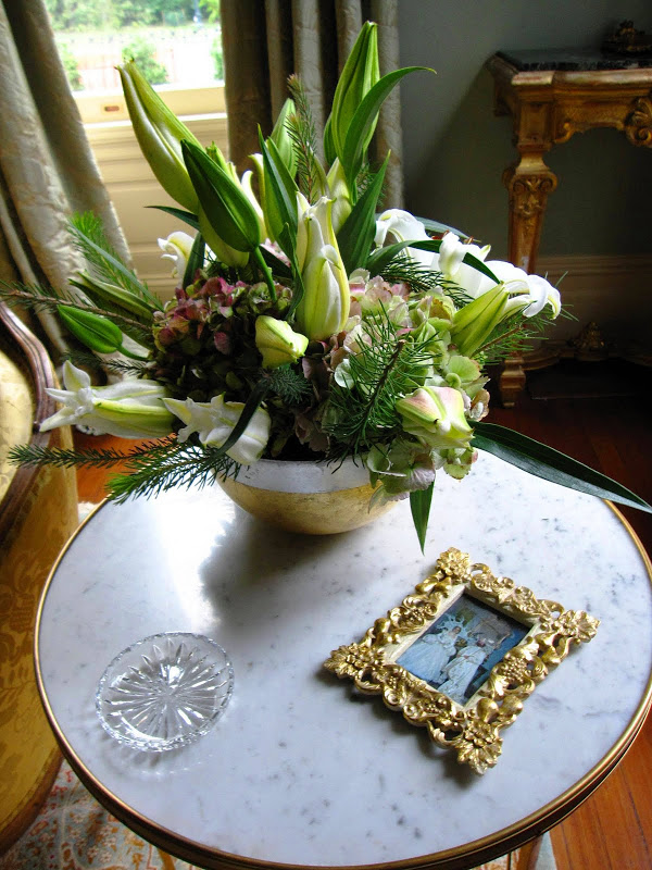 Ladies parlor in a historic New Orleans mansion with a flower arrangement in a porcelain bowl with hydrangeas and white star gazer lilies and pine sprigs