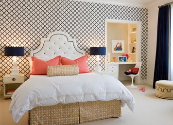 Bedroom by Massucco Warner Miller with blue and white lattice print wallpaper, dark blue curtains, white upholstered headboard with navy trim and coral accent pillows