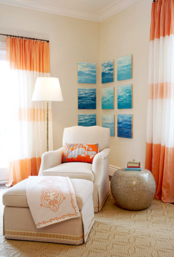 Bedroom by Massucco Warner Miller with orange and cream striped curtains, a white armchair with matching ottoman and an orange accent pillow