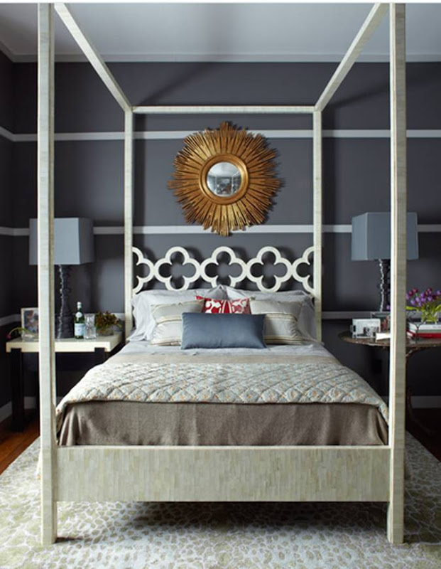 Bedroom with dark grey walls with white stripes, a white canopy bed, a sunburst mirror, mismatched nightstands and a white and tan rug