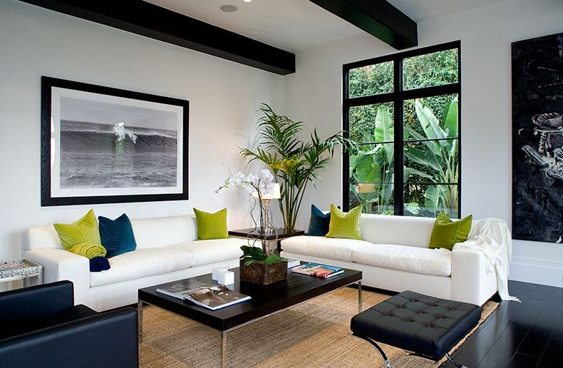 Black and white living room in a Spanish Revival home with a sea grass rug and green and blue accent pillows