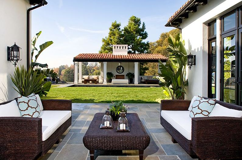 Outdoor seating area with wicker sofas with white cushions in a Spanish revival style home in Los Angeles