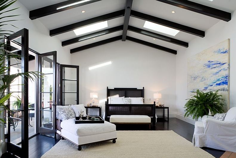 Master bedroom in a Spanish Revival home with exposed painted black beams and black glass doors opening up to a patio