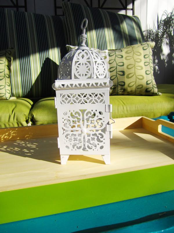 White metal Moroccan lantern on a bright green tray