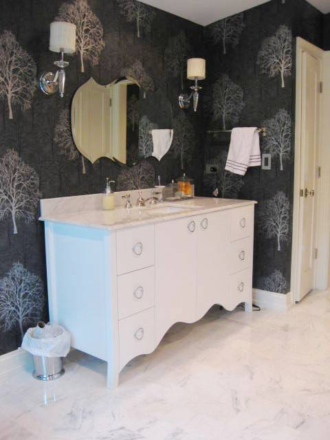 Black master bathroom with white cabinets and moldings and Carrara marble floor