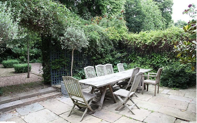 Long teak outdoor dining table sits in the paved part of the garden near the kitchen