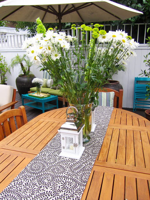 Tall  floral arrangement with white daises and pom poms on a teak patio table