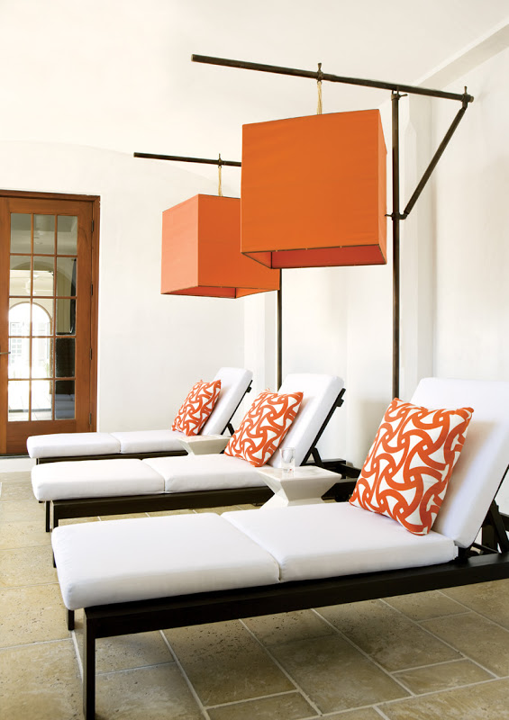 Outdoor chaise lounge chairs with orange Trina Turk designed Santorini outdoor fabric pillows