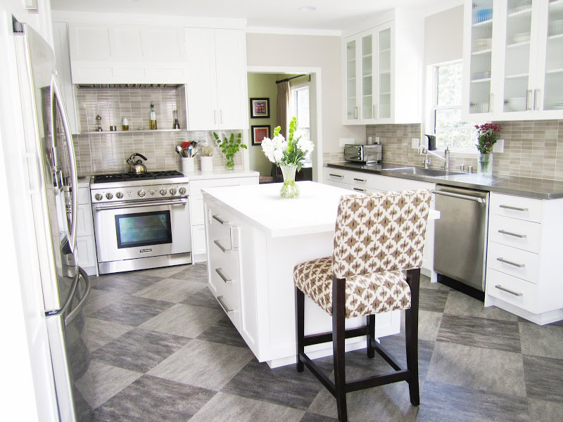 Gourmet kitchen with Thermador oven, grey/brown backsplash, white paneled cabinets and hood and grey tiles arranged in a diamond pattern